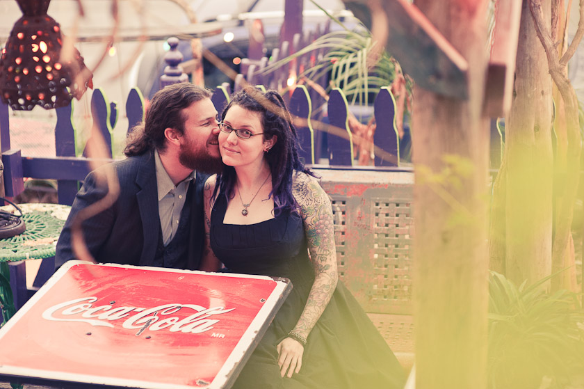 man kissing woman, at the coca cola table