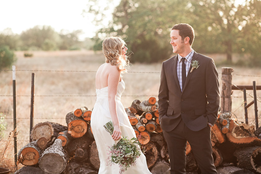 bride and groom in front of firewood