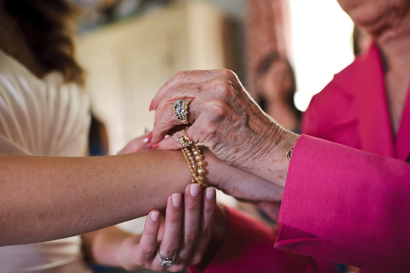 grandma putting bracelet on bride