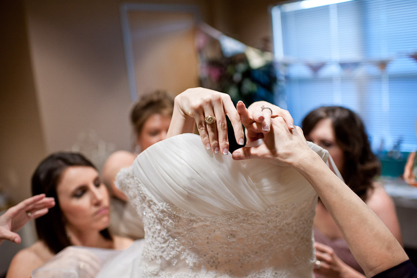 getting into the wedding dress with the help of mother of bride and bridesmaids