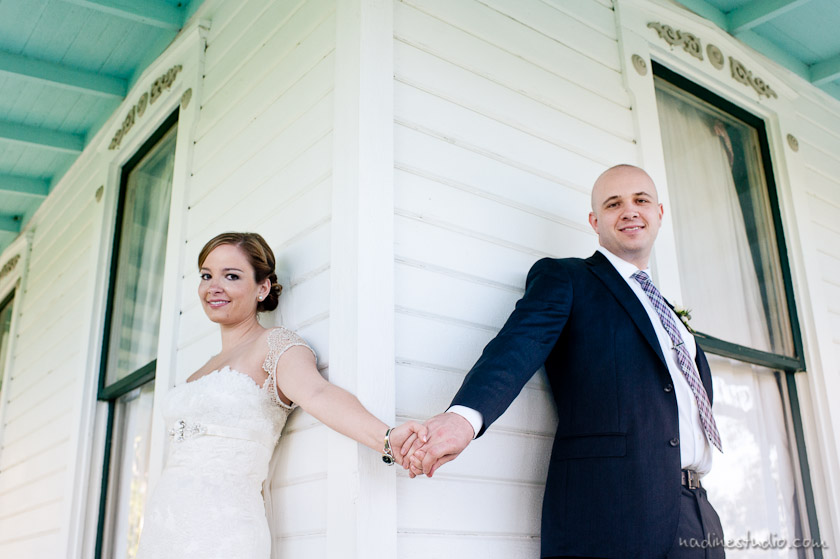 bride and groom holding hands and not seeing each other