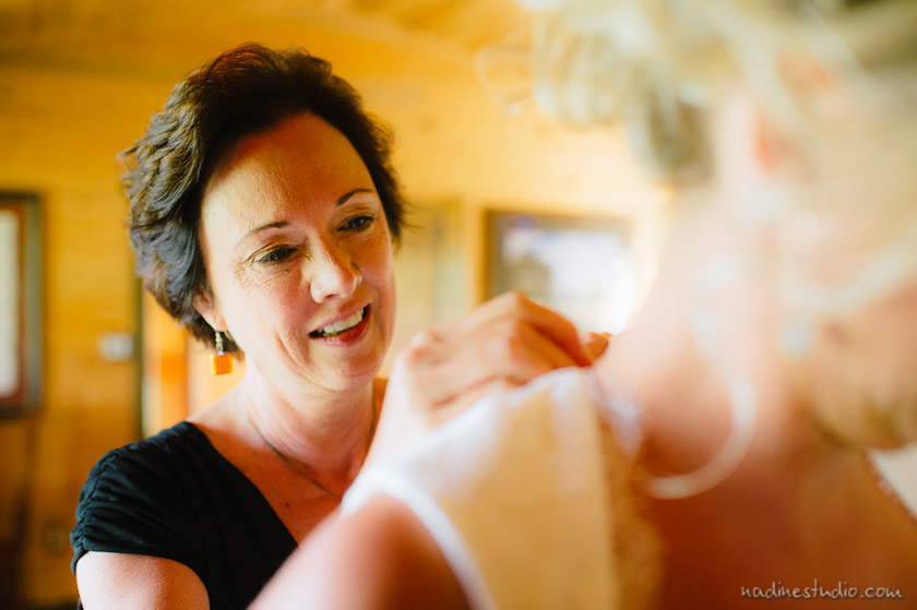 mother of the bride helping bride dress