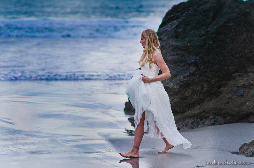 bride walking on the beach with the sun setting