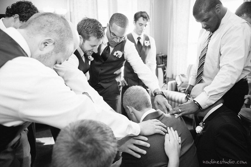 groomsmen praying over the groom