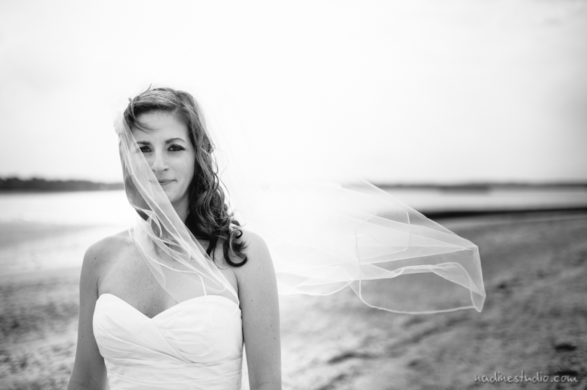 black and white beach bride portrait, veil flying in the wind