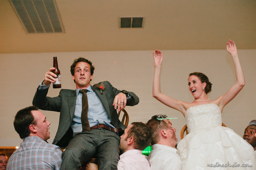 bride and groom lifted up in a chair, groom looking shocked