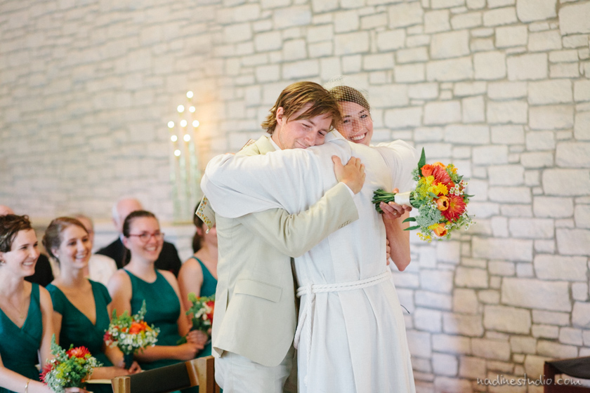 officiant hugging bride and groom