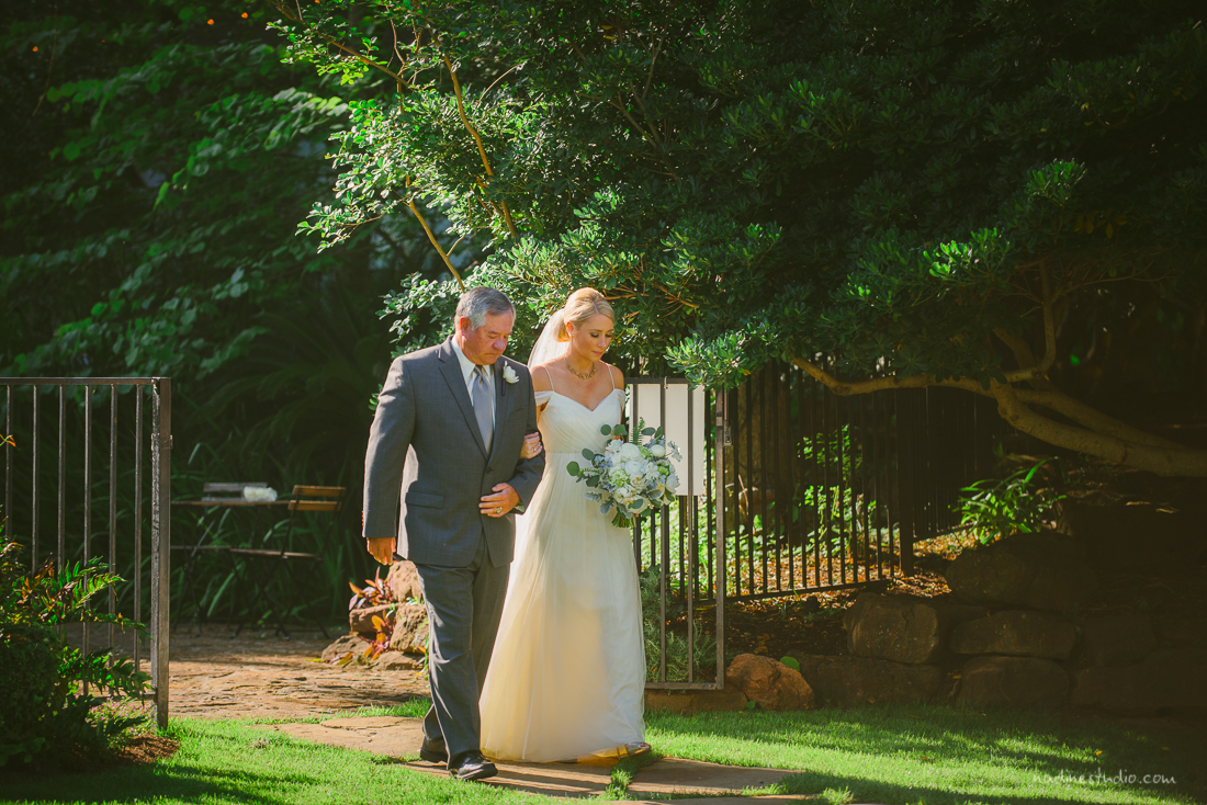 a graceful bride walking down the aisle with her father