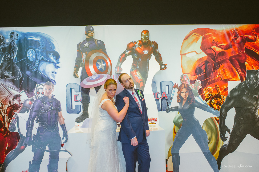 bride and groom in front of the avengers poster at the highball
