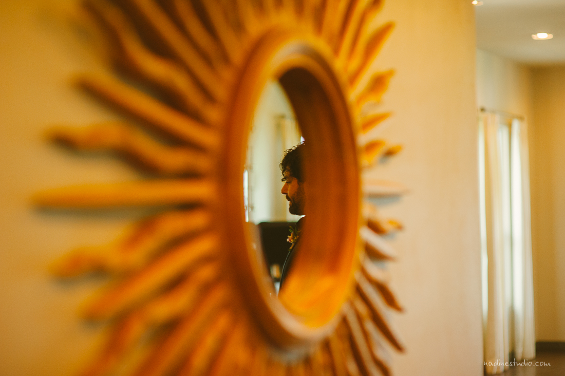 refelection of the groom in a sun mirror