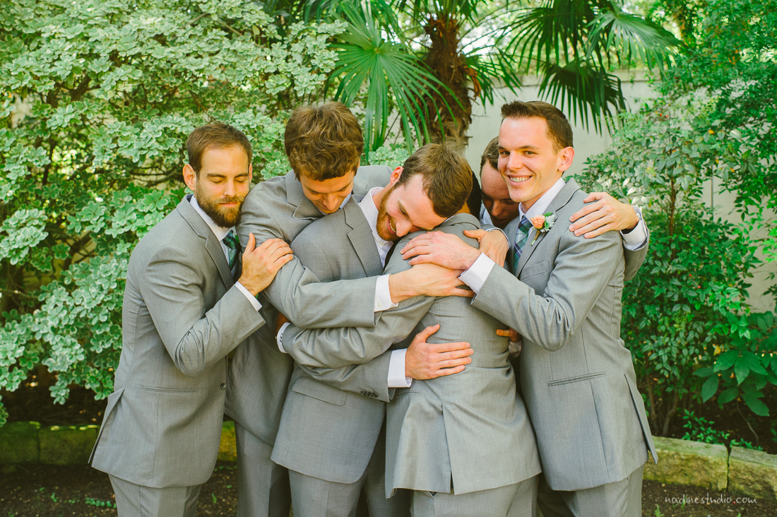 hugging groomsment in a gray suit