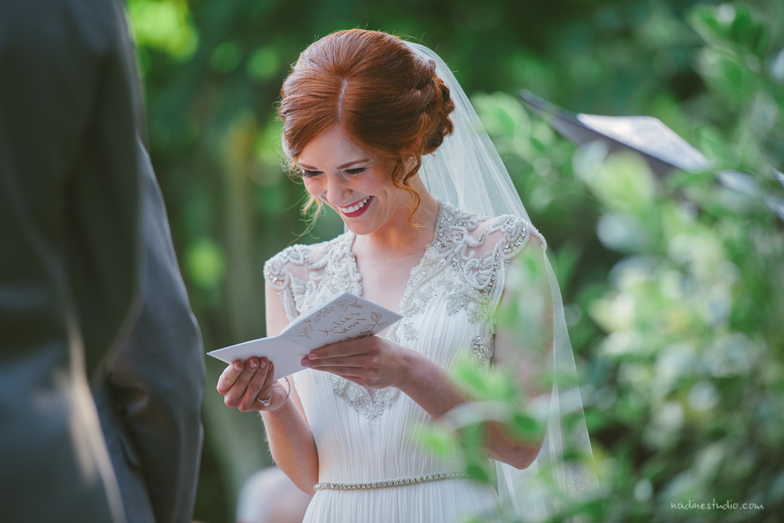 bride smiling as she reads her vows