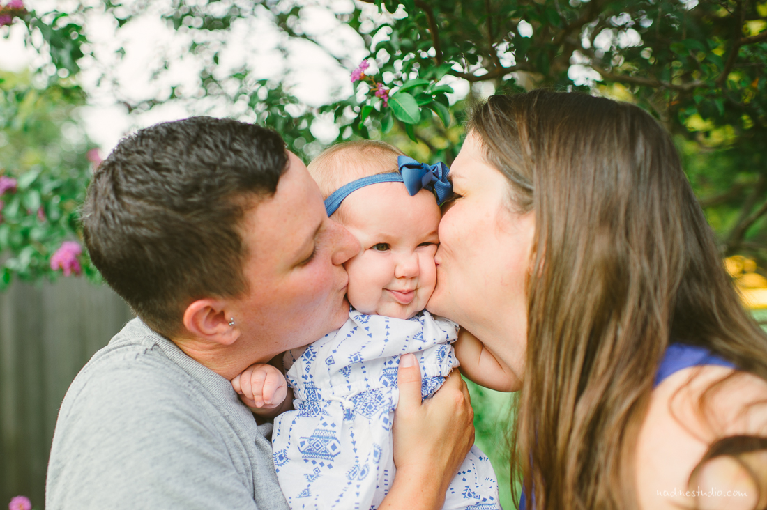 both mothers kissing child
