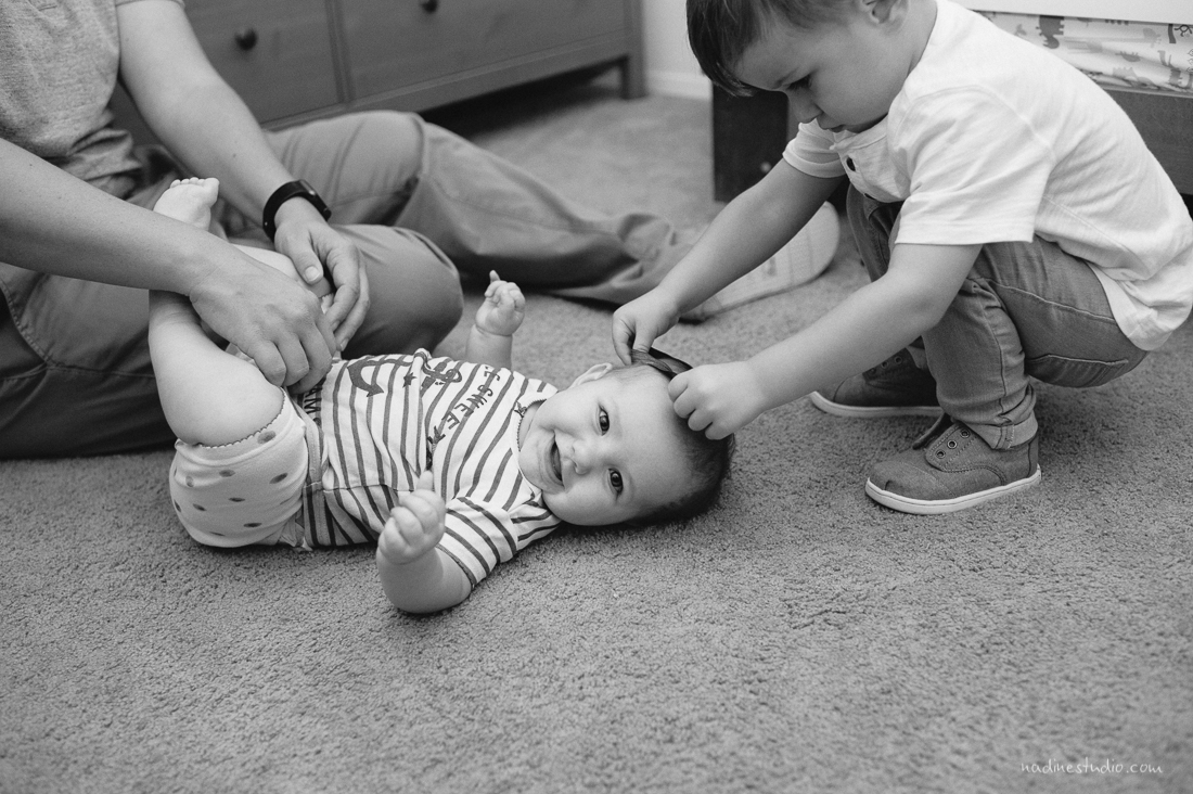 brother helping baby dress