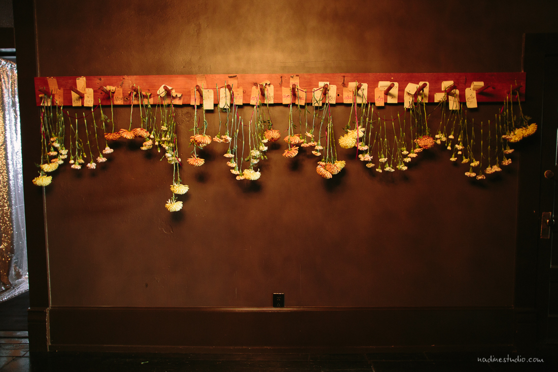 string of flowers hanging on a wall