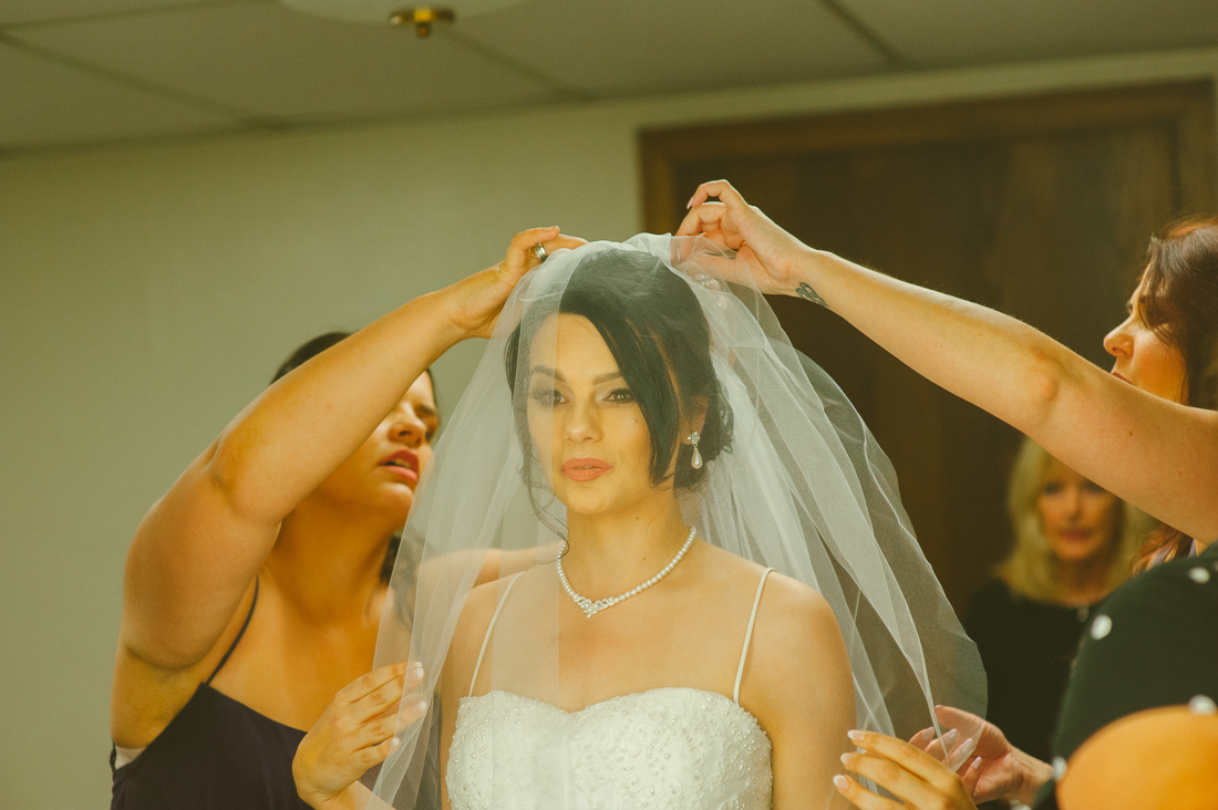the bride putting on the veil