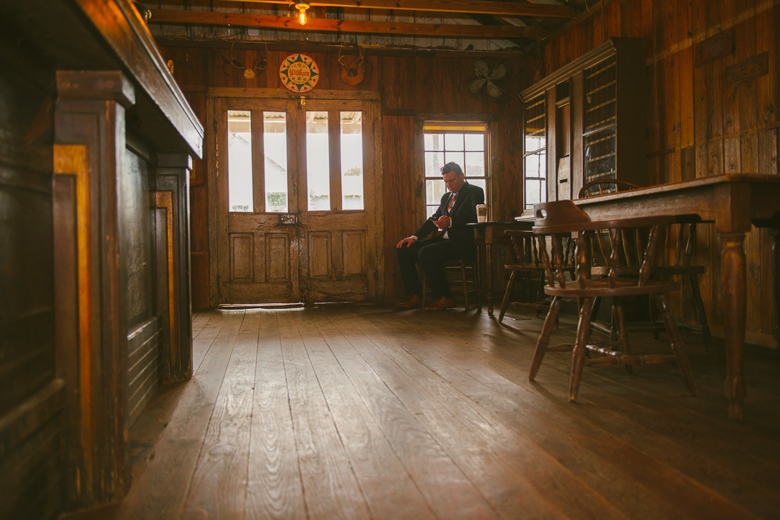 groom waiting in a dimly root room in a ranch