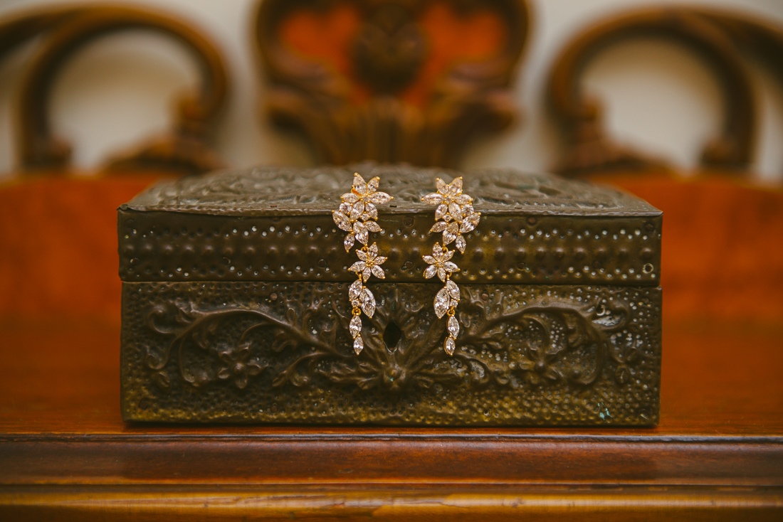 bridal earrings on a wooden chest
