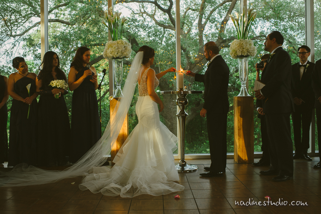 ceremony inside a glass house with a giant tree