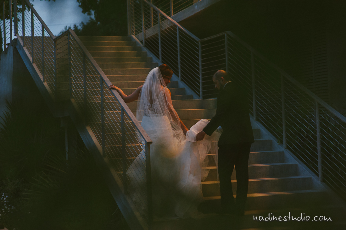 bride and groom walking up large stairs in a dreamy fashion